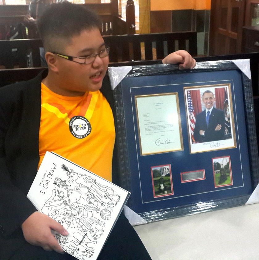 Malaysia's first autistic savant artist, Delwin Cheah Wien Loong, 11, shows the letter of recognition he received from United States President Barack Obama dated July 14, and a photograph signed with well-wishes. — Bernama pic