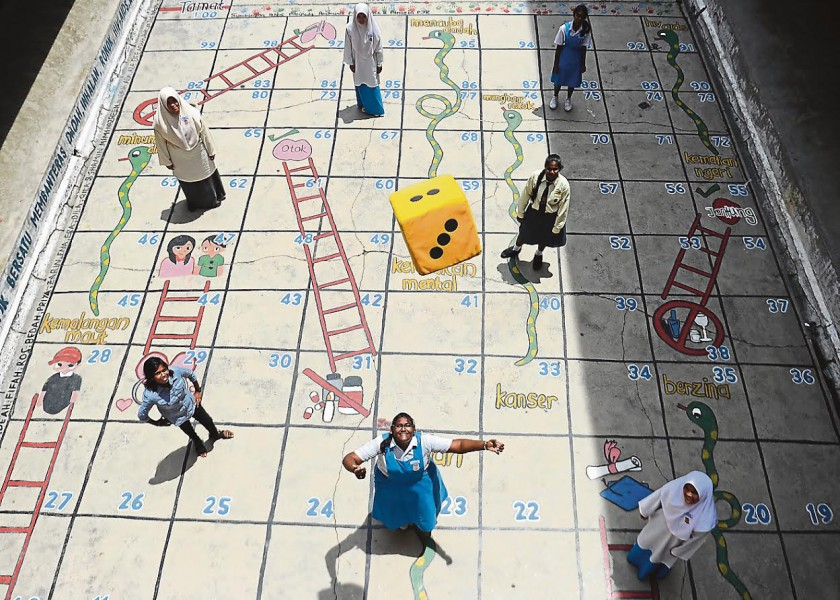 Students play Snakes and Ladders at SMK (P) Kapar in Klang. A psychologist says a happy child is a successful child. — Bernama pic