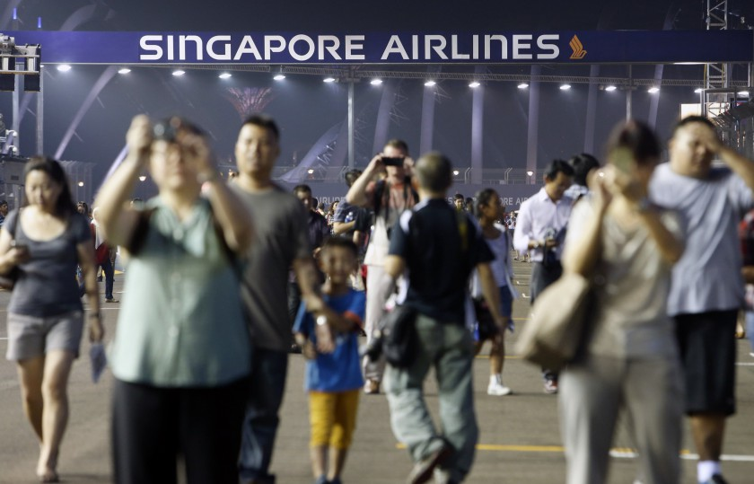 Fans take photos in the circuit during a pit walk ahead of the Singapore F1 Grand Prix night race September 18, 2014. Singapore will be counting on its marquee Formula One race to help make up for a 30 per cent drop in Chinese tourists this year. — Reut