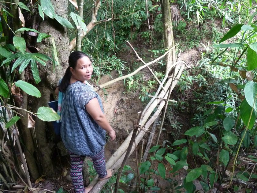 Tarihing Masanim makes her way barefoot across a river in her village of Sonsogun Magandai, October 4, 2014. — Picture courtesy of Sabah Women Entrepreneurs and Professionals Association