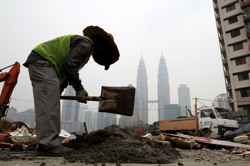 A foreign worker gets on with his daily task at a residential area that was demolished for development on a hazy day in Kuala Lumpur in this October 7, 2014 file picture. — Picture by Yusof Mat Isa