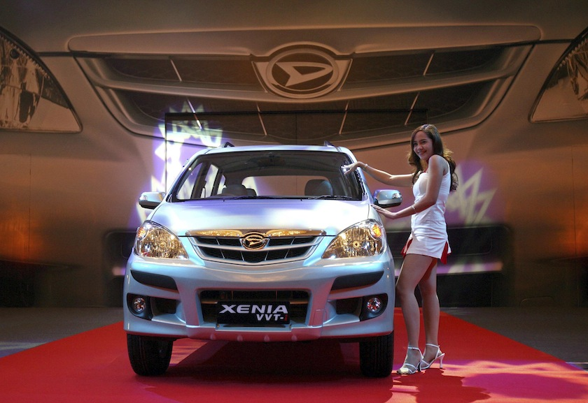 A girl stands beside the Daihatsu passenger car named Xenia during its launch in Jakarta in this July 12, 2006 file photo. — Reuters pic