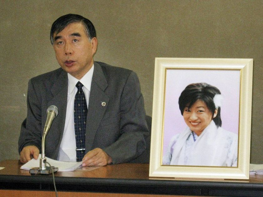 """Japanese lawyer Hiroshi Kawahito speaks at a press conference in Tokyo on October 17, 2008, while a portrait of Japanese nurse Ai Takahashi, a victim of """"karoshi"""" or death by overwork is displayed. — AFP pic"""