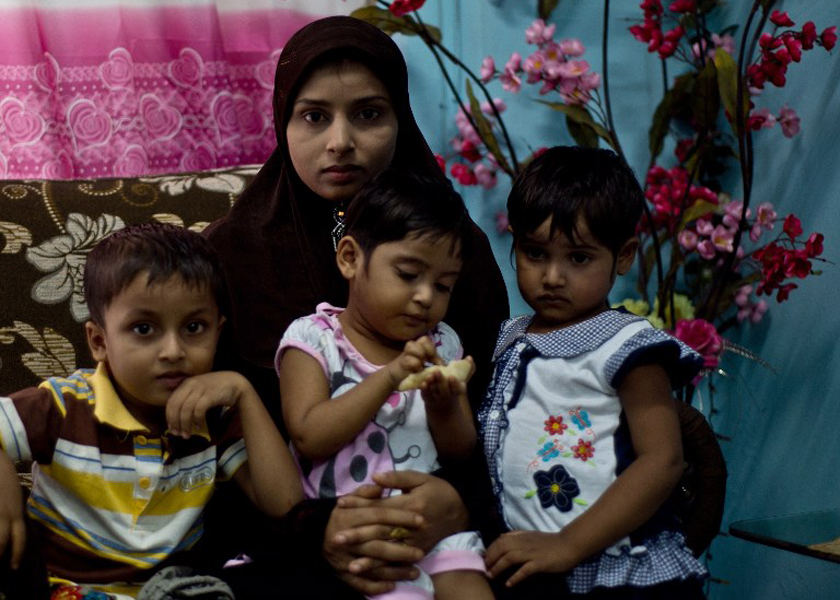 Bibijan Rahimullah, 27, poses with her three children. Bibijan stepped aboard a small boat in Myanmar for what she was told would be a week-long journey to Malaysia to escape violence, November 30, 2014. — AFP pic
