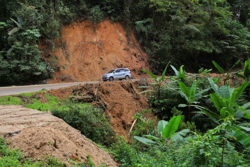 File picture shows car driving past a section of the road where a small landslide occurred at the Cameron Highlands. — Picture by Saw Siow Feng