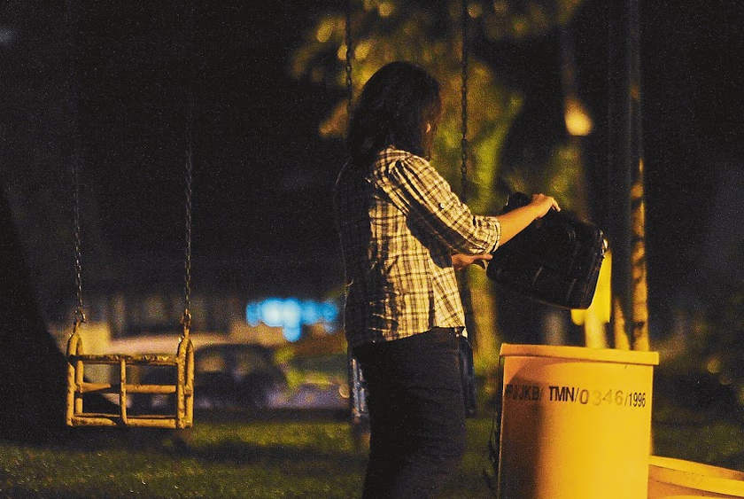 In a re-enactment, a 'victim' drops a bag of money into a dustbin as instructed by the fraudster.