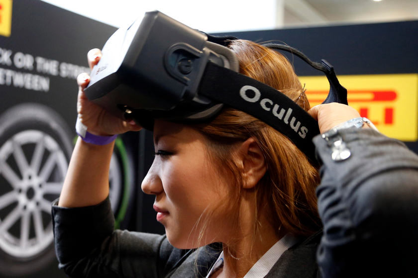 A woman puts on an Oculus virtual reality headset for the 2014 LA Auto Show November 21, 2014. — Reuters pic