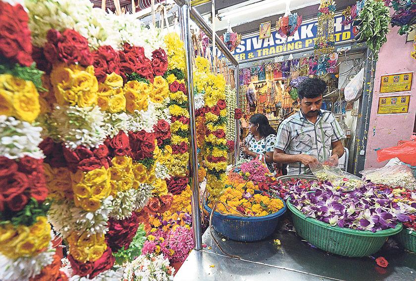 An Indian vendor prepares flower garlands for Hindu devotees in Little India. — AFP pic