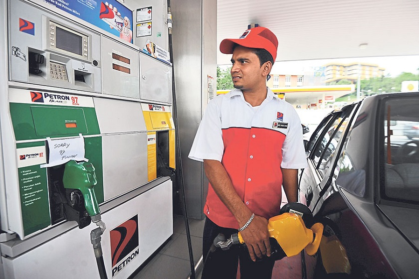 Pump attendant Muhd Babul Khan, 26, who works at a petrol station in Petaling Jaya, fills a car with RON95 but a sign at the green pump says it has run out of RON97.  — Picture by Azinuddin Ghazali