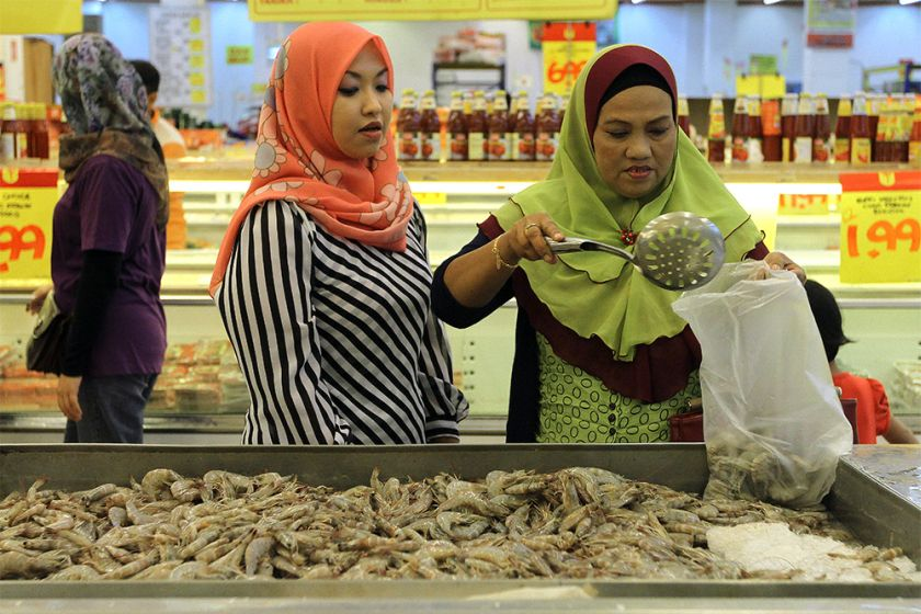 Two women are seen buying fish in Kelantan. A news report by Sinar Harian had in 2014 then stated that the rules for female Muslim traders and staff in Kelantan include wearing a tudung or headscarf that covers their chests, wearing long-sleeves, wearing loose-fitting pants and skirts or clothing that do not show their body shape. ― Picture by Yusof Mat Isa