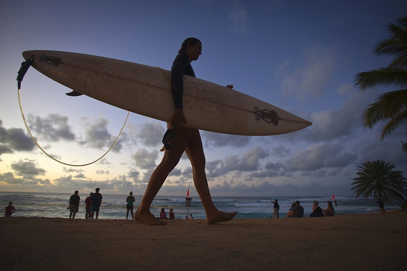 A female surfer walks out of the Pacific Ocean after spending time surfing the North Shore of Oahu in Pupukea, Hawaii December 13, 2014. — Reuters pic