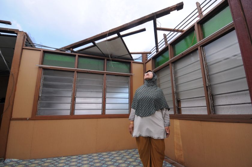 Masriyah Harun looks up at her missing roof, which was swept away by last night's windstorm in Balik Pulau, Penang. December 30, 2014. — Picture by K.E. Ooi