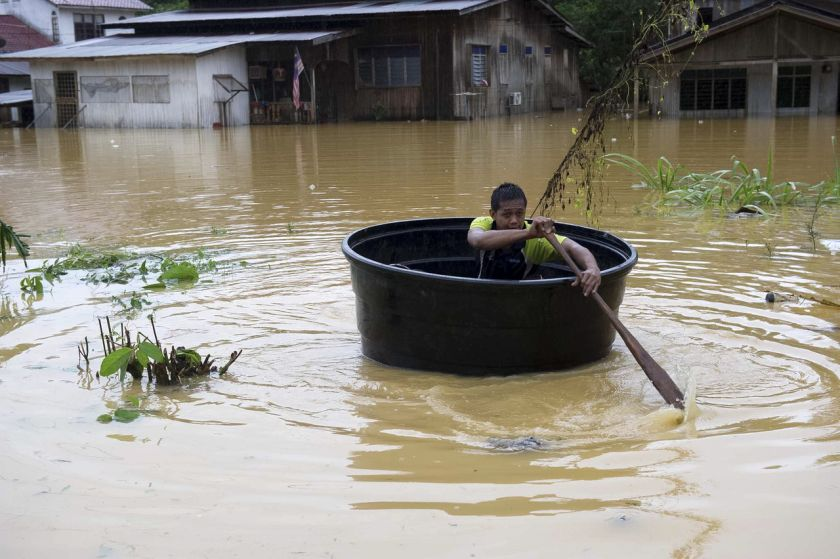 A resident of Kampung Keroh uses a water tank to save himself as flood waters continue to rise, December 25, 2014. ― Bernama pic