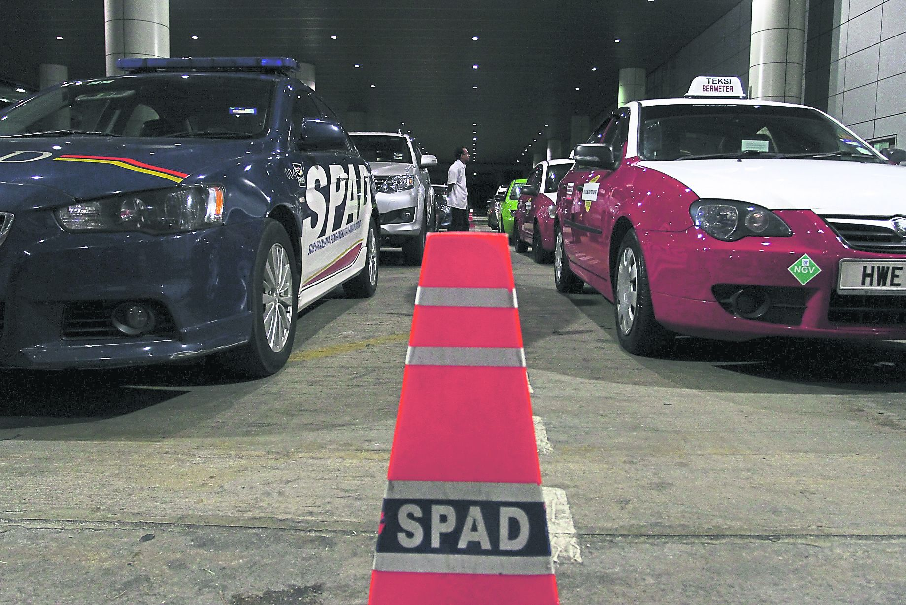 A SPAD official inspects illegal taxis during Ops Parasit. — Picture by Azneal Ishak