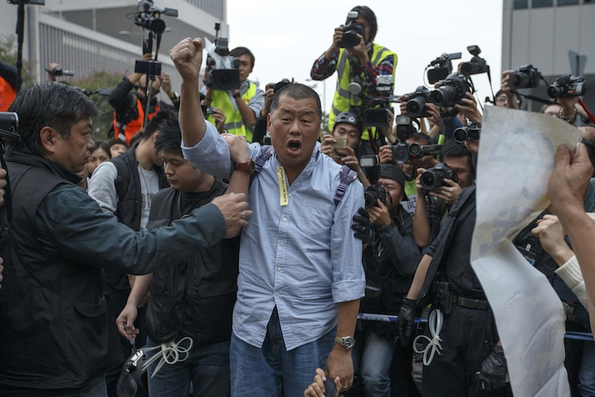 Tycoon and Apple Daily Newspaper owner Jimmy Lai shouts slogan before he is taken away by police officer at an area previously blocked by pro-democracy supporters, outside the government headquarters in Hong Kong, December 11, 2014. —Reuters pic