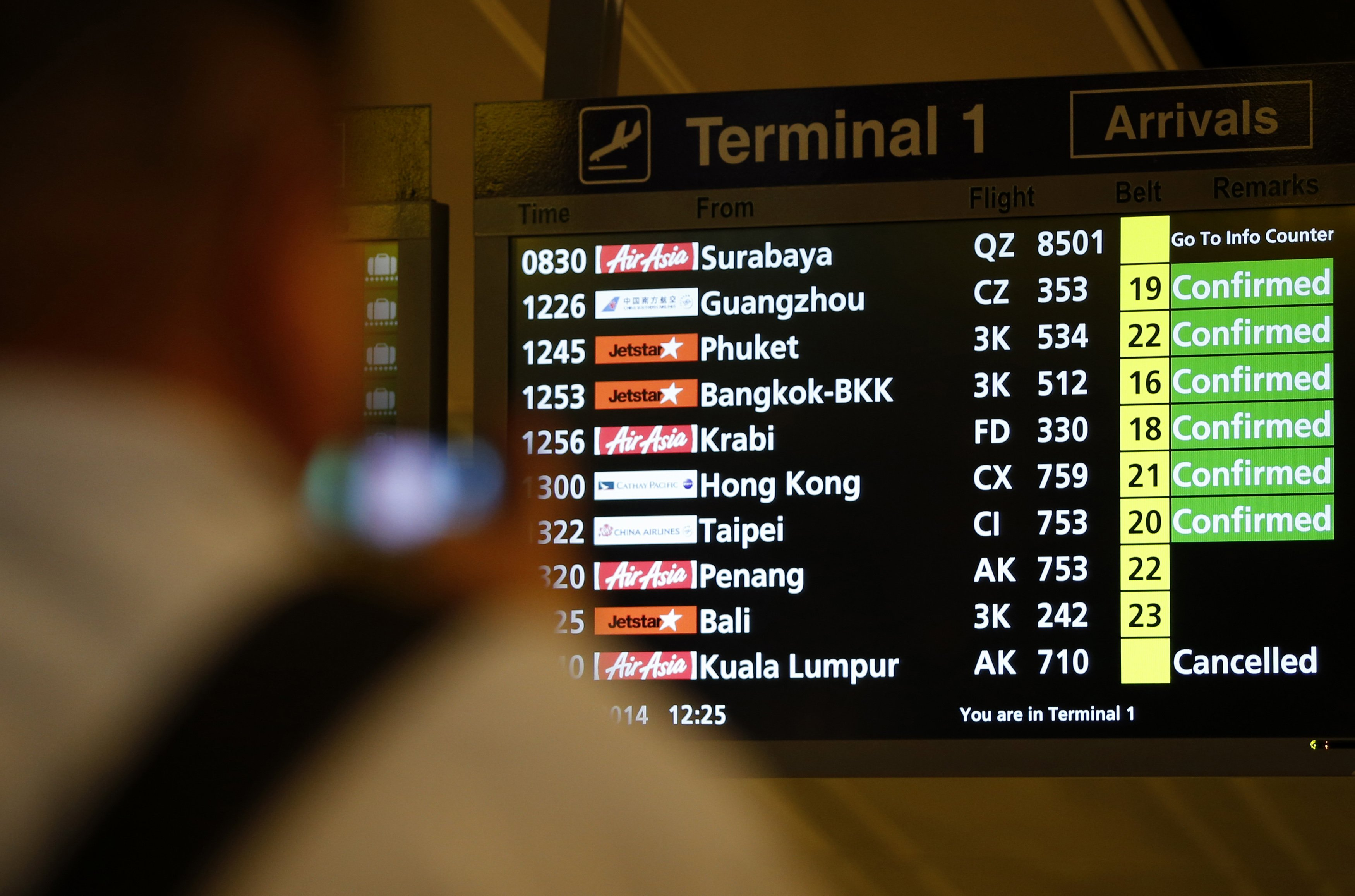 A flight arrival information signboard shows the status of AirAsia Flight QZ8501 from Indonesian city of Surabaya to Singapore at Changi Airport December 28, 2014. — Reuters pic
