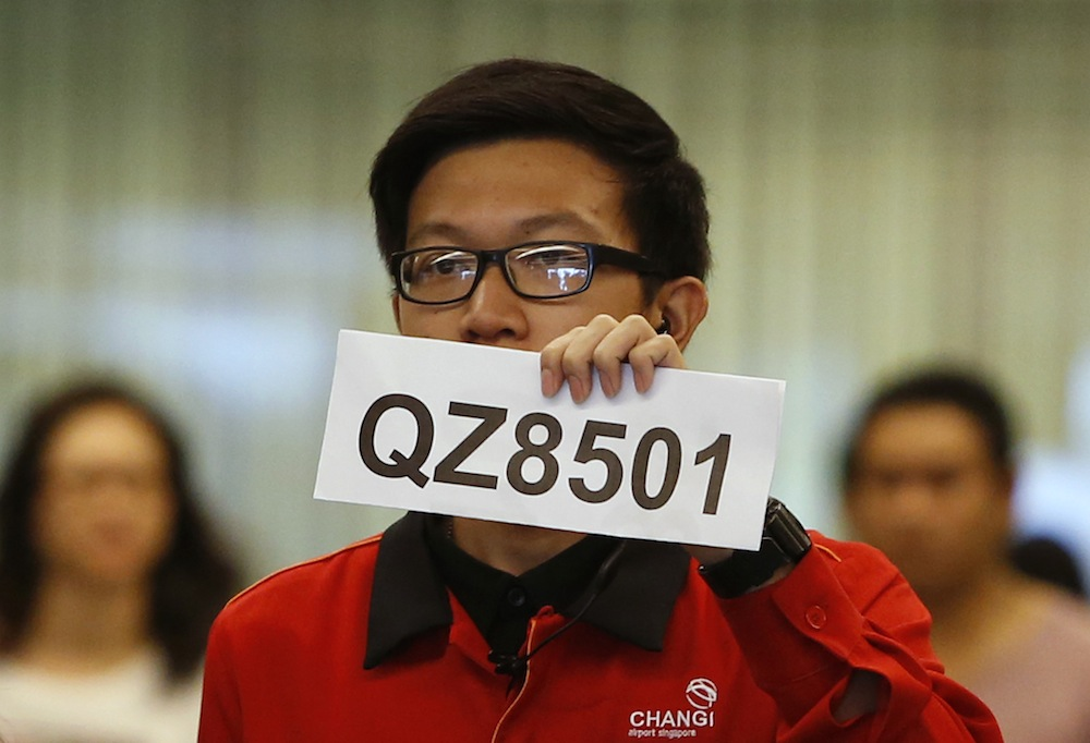 A Changi Airport staff holds up a sign to direct possible next-of-kin of passengers of AirAsia flight QZ 8501 from Indonesian city of Surabaya to Singapore, at Changi Airport in Singapore December 28, 2014. — Reuters pic