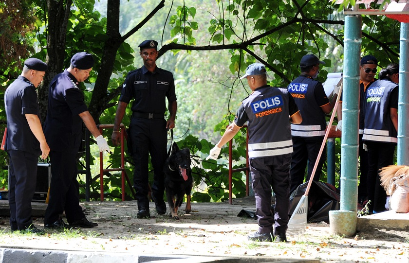 Police personnel are seen investigating a crime scene. Chef Mo Yi Hong and his son Wei Qiang have been charged with murder over the death of a would-be robber who broke into their Seremban home on February 24. ― File pic