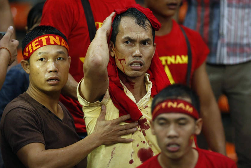 A Vietnamese fan wipes blood on his head after scuffles between fans at the Suzuki Cup semi-final between Vietnam and Malaysia at the Shah Alam stadium, December 7, 2014. — Reuters pic