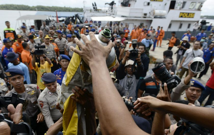 Police carry debris from a boat believed to be from the AirAsia QZ8501 jet on January 1, 2015 in this photo taken by Antara Foto. ― Reuters pic