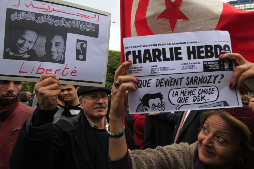 People hold up signs during a demonstration to protest against the disappearance of two Tunisian journalists, and the attack in Paris on satirical French newspaper Charlie Hebdo, in Tunis, January 9, 2015. — Reuters pic