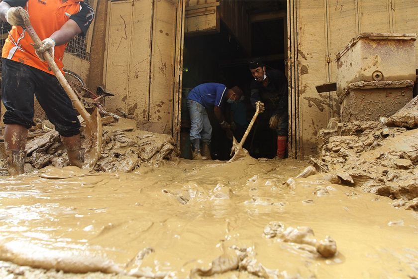 Residents and volunteers are seen shovelling mud out from the houses.