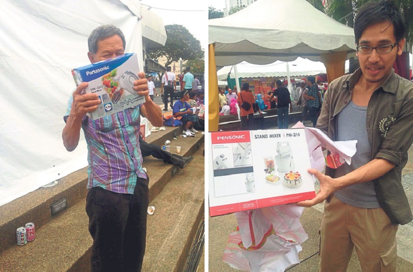 Two of the homeless men show off the electrical appliances given to them. — Picture by Malay Mail