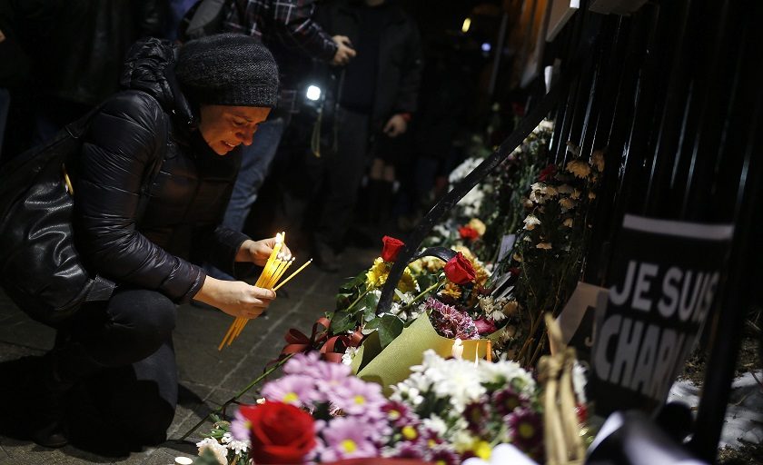 A woman cries as she lights candles to pay tribute to the victims following a shooting by gunmen at the offices of weekly newspaper Charlie Hebdo in Paris, in front of the French embassy in Sofia January 9, 2015. — Reuters pic
