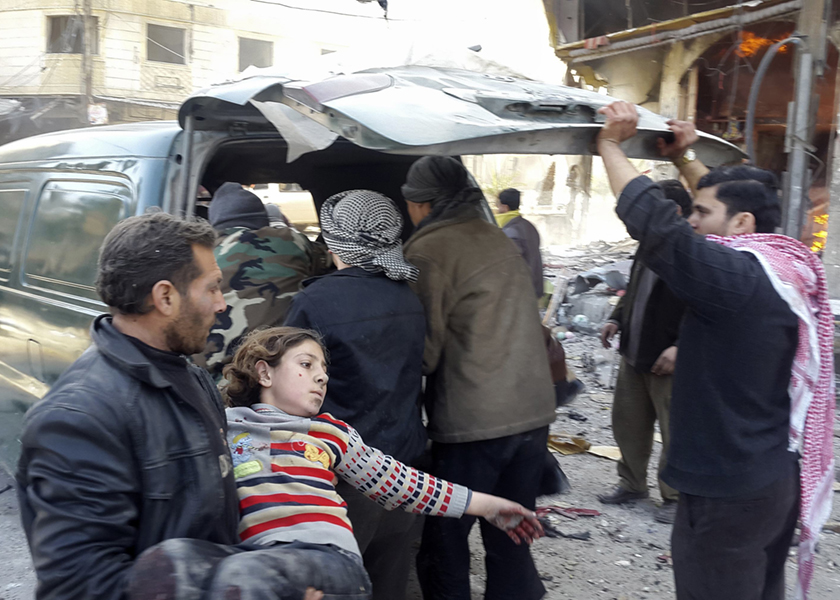 A man carries an injured child after shelling by forces loyal to Syria's President Bashar al-Assad in Hamouria, near Damascus, January 23, 2015. — Reuters pic