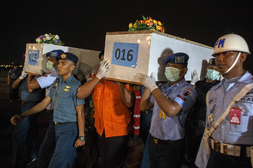 Indonesian military personnel carry caskets containing the remains of passengers who were onboard AirAsia flight QZ8501, recovered off the coast of Borneo, at a military base in Surabaya, January 2, 2015. ― Reuters pic