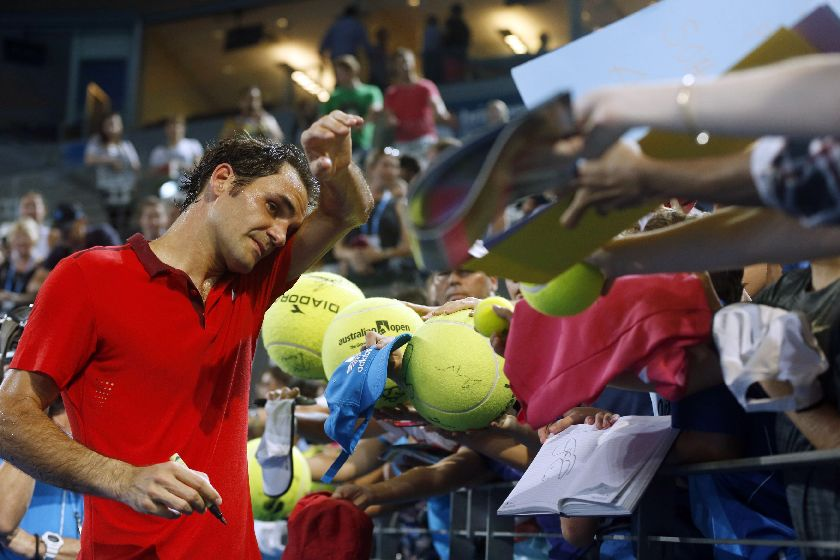 Roger Federer of Switzerland wipes sweat from his brow as he signs autographs after he defeated John Millman of Australia at the Brisbane International tennis tournament January 8, 2015. — Reuters pic