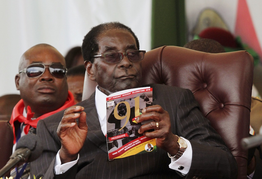 Zimbabwe President Robert Mugabe holds a booklet during his 91st birthday celebration in Victoria Falls February 28, 2015. — Reuters pic
