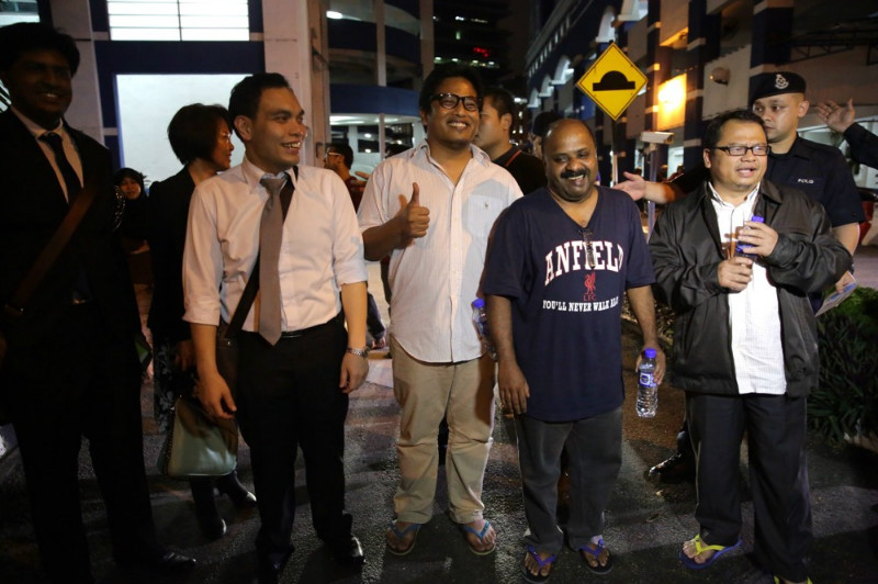 TMI editors (from right) Zulkifli Sulong, Lionel Morais, Amin Shah Iskandar, walking out with their lawyer Syahredzan Johan after their release from the Dang Wangi police station, Kuala Lumpur, March 31, 2015. — Picture by Choo Choy May