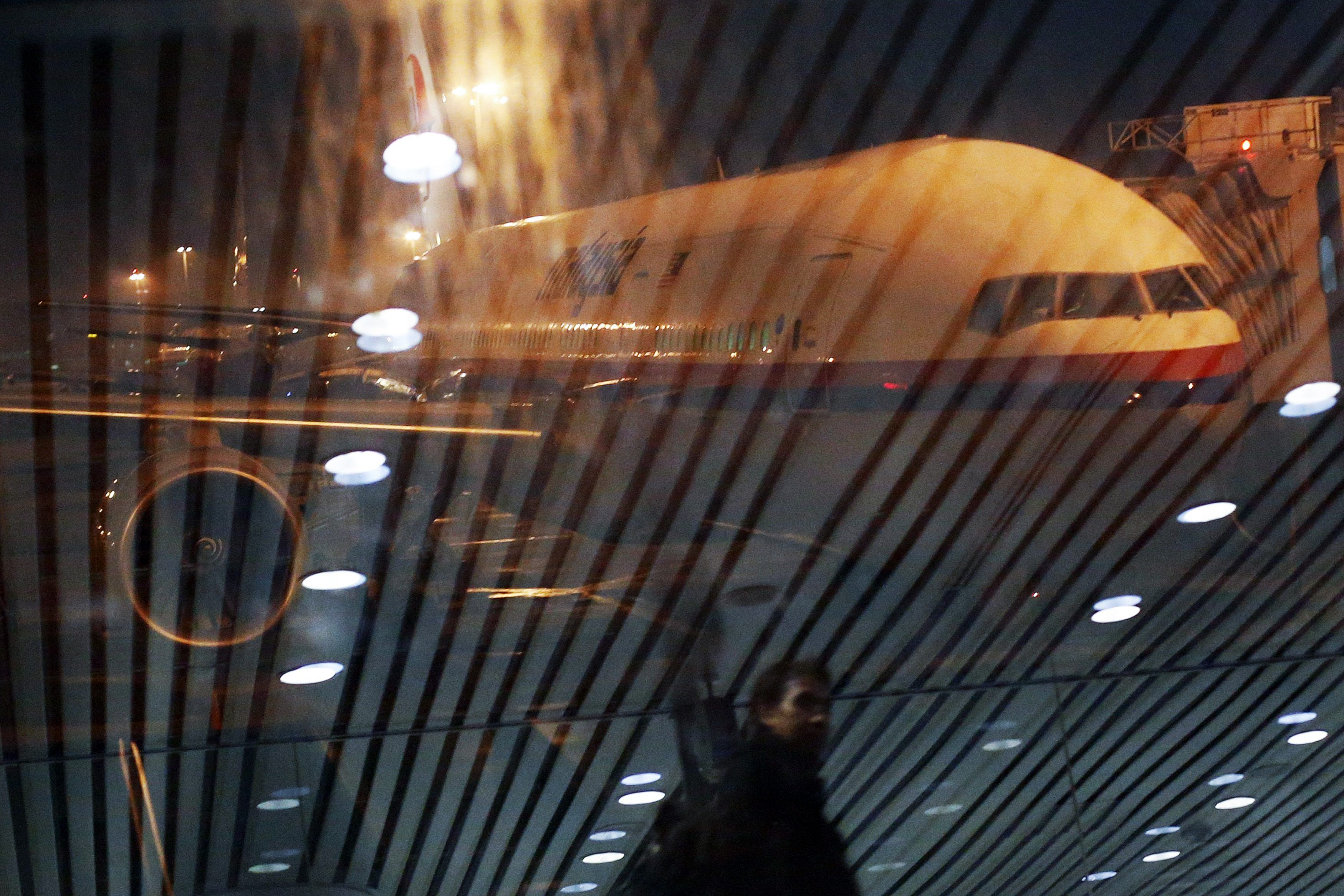 Malaysia Airlines Boeing 777-200ER flight MH318 to Beijing sits on the tarmac as passengers are reflected in the glass at the boarding gate at Kuala Lumpur International Airport at approximately 12:20am in this March 17, 2014 file photo. — Reuters pic