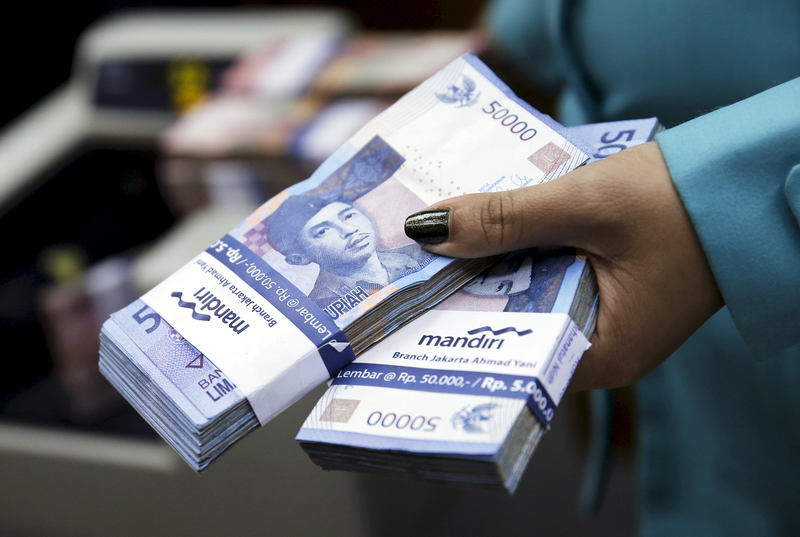 A woman holds Indonesian rupiah notes at a money changer in Jakarta, March 23, 2015. — Reuters pic