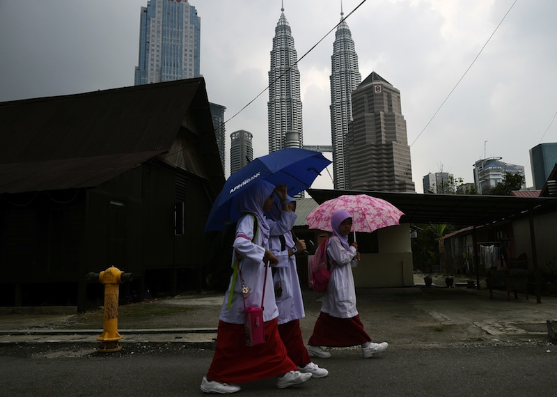 Malaysian schoolgirls take shelter under umbrellas as they return from school at the Kampung Baru neighbourhood of Kuala Lumpur on March 23, 2015. —AFP pic