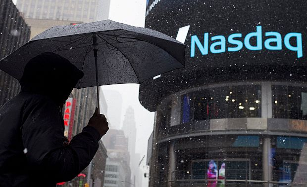 A man uses an umbrella to guard against snowfall as he walks past the Nasdaq MarketSite in Times Square, Midtown New York March 20, 2015. — Reuters pic