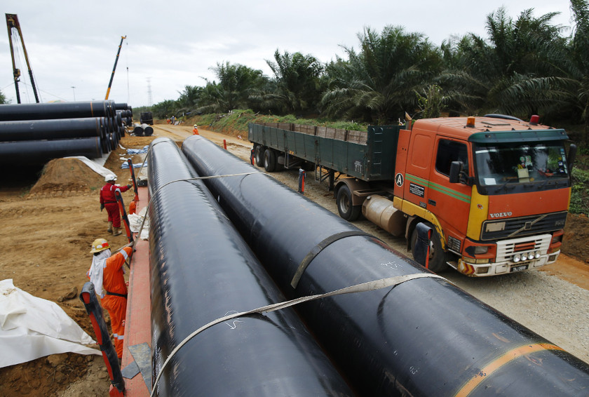 Workers transport oil pipelines to be laid for the Pengerang Gas Pipeline Project at an area 40km away from the Pengerang Integrated Petroleum Complex in Pengerang, Johor, February 4, 2015. — Reuters pic