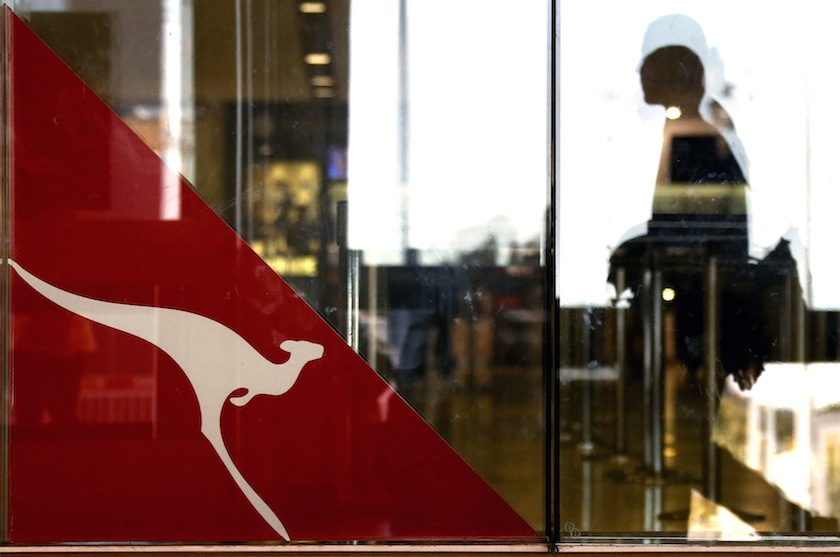 A passenger walks past a Qantas Airways logo at the Sydney International Airport terminal in this July 18, 2014 file photo. — Reuters pic