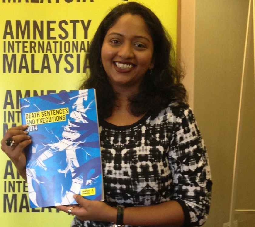Amnesty International Malaysia executive director Shamini Darshni poses with the 2014 report on the death penalty. — Picture by Melissa Chi
