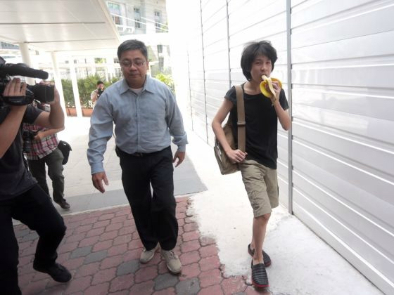 Amos Yee eating a banana as he enters Singapore's State Courts with his father for his pre-trial conference on April 17, 2015. — Jason Quah/TODAY pic