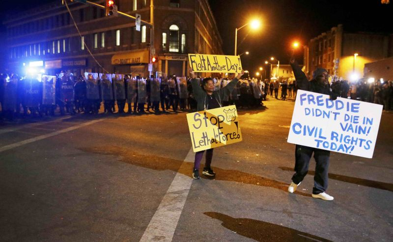 Protesters hold up signs in front of a line of police in Baltimore, Maryland, April 28, 2015. ― Reuters pic