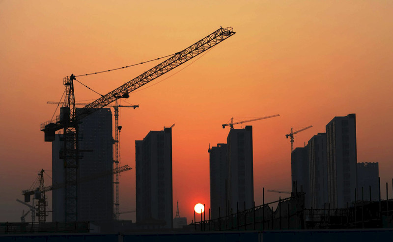 The sun sets behind a residential construction site in Rizhao, Shandong province April 14, 2015. — Reuters pic