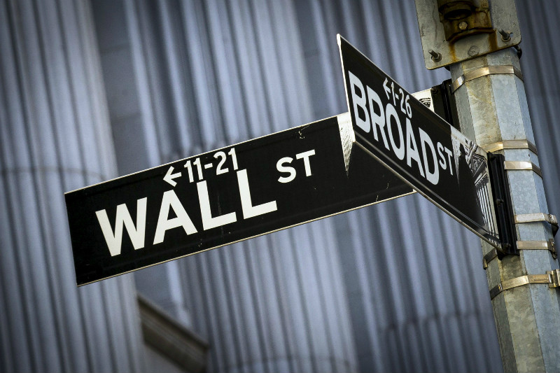 The street signs for Wall St and Broad St hang at the corner outside the New York Stock Exchange on March 24, 2015. — Reuters pic
