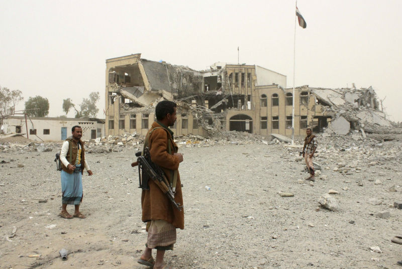 Police troopers stand near the building of police headquarters, destroyed by Saudi-led air strikes, in Yemen's northwestern city of Saada April 14, 2015. — Reuters pic
