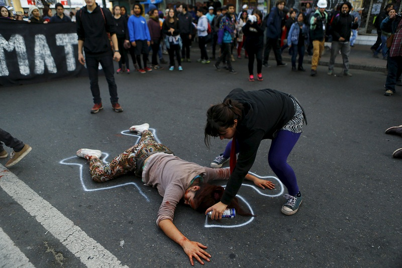 A demonstrator sprays an outline around another protester pretending to be dead, in reference to a student shot dead on May 14 after a protest march, as Chile's President Michelle Bachelet delivers a speech inside the National Congress, in Valparaiso city, May 21, 2015. — Reuters pic