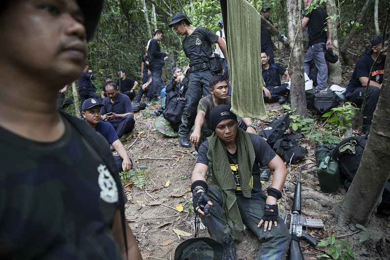 Policemen rest after hiking to the abandoned human trafficking camp in the jungle close the Thailand border at Bukit Wang Kelian in northern Malaysia May 26, 2015. — Reuters pic