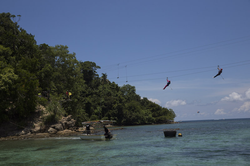 Tourists ride a zip line from Pulau Gaya to Pulau Sapi, off Kota Kinabalu. Sabah's porous security has been a long-standing issue for the past 53 years and remains unsettled till today. — Picture by Adam Dean/The New York Times