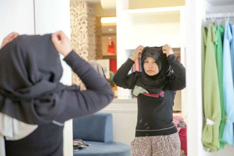 A customer tries on a hijab at the Naelofar Taman Tun Dr Ismail store on April 29, 2015.