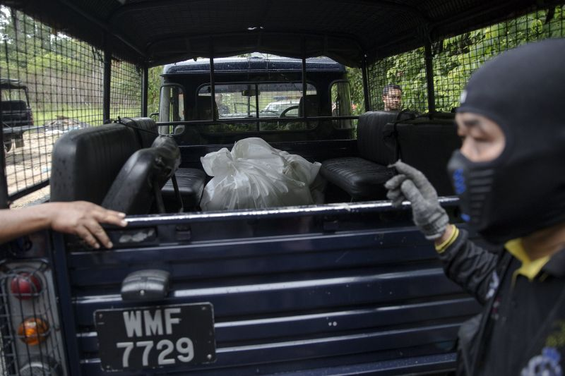 A police forensic team transport body bags with human remains at Bukit Wang Burma in northern Malaysia May 27, 2015. ― Reuters pic